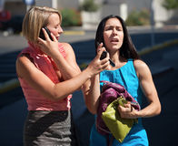 Beautiful women talking on phones in city Royalty Free Stock Image