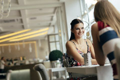 Beautiful women talking in restaurant. Before ordering a meal royalty free stock images