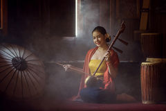 Beautiful women in traditional dress costume playing treble fiddle. Treble fiddle or soprano sounded string Thai music instrument stock images