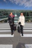 Beautiful women Traveling - Walking With Luggage At Airport Car. Beautiful twins women Traveling - Walking With Luggage At Airport Car Park Stock Photo