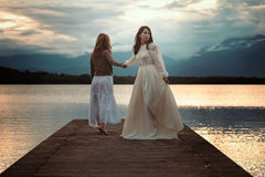 Beautiful women walking on lake pier Stock Image