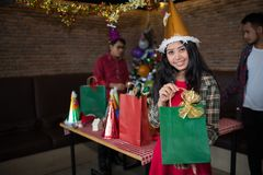 Beautiful woman wear red dress and santa claus hat showing green gift bag on hand in restaurant. royalty free stock images