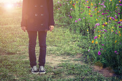 Beautiful women wearing black coat, standing in a field of flowe Stock Image