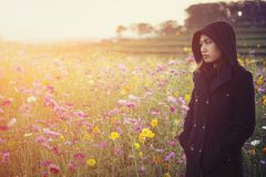 Beautiful women wearing black coat, standing in a field of flowe Stock Photography