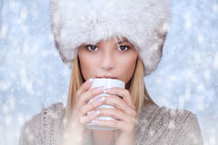 Beautiful women wearing warm clothing and fur hat,is taking a hot drink Stock Image
