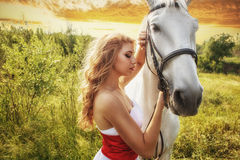 Beautiful women with white horse over sunset Royalty Free Stock Image