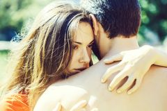 Pretty girl hugs muscular man. Beautiful women young female brunette model with brown eyes hugs men with nude muscular body on sunny day stock images