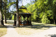 Beautiful wooden arbour and  trees in the park in autumn. Royalty Free Stock Photo