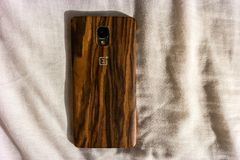Beautiful wooden back design of the OnePlus smartphone royalty free stock photo