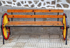 Beautiful wooden bench with colorful painted wheels. For decoration stock photos