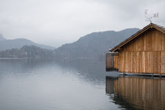 Beautiful wooden boathouse floating on lake bled in fog winter scenery. Dramatic cloudy wonderful landscape zen view on wooden boathouse floating on lake bled Royalty Free Stock Photos