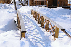 Beautiful wooden bridge from cedar across the river on a sunny winter day. Royalty Free Stock Photography