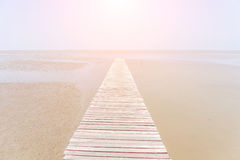 Beautiful wooden bridge extending into the sea with soft sunligh Stock Image