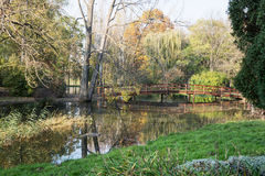 Beautiful wooden bridge over mirrored pond in the european autum Royalty Free Stock Photography