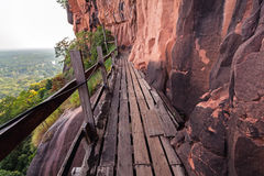 Beautiful Wooden bridge in red cliffside at Wat Phu tok mountain. Bueng Kan, Thailand Stock Photos