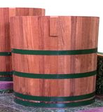Beautiful wooden bucket on the marble floor. Close to the old wooden tank, the two ancient shapes, which are imitation, placed on the floor of a marble staircase stock photo