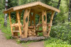 Beautiful wooden carved arbor on the terrenkur health trail along the Belokurikha mountain river. Belokurikha, Russia - July 30, 2015: Beautiful wooden carved Royalty Free Stock Images