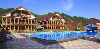Beautiful wooden cottages with swimming pool in the mountains. Royalty Free Stock Photos