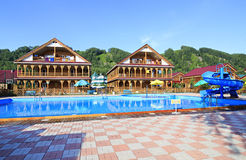 Beautiful wooden cottages with swimming pool in the mountains. Royalty Free Stock Image
