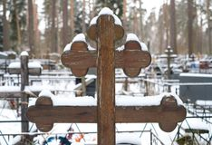 Beautiful wooden cross of traditional shape and artificial flowers on the grave of the Orthodox cemetery in winter. stock images