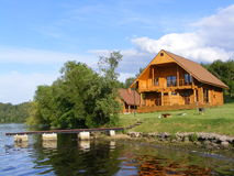Beautiful wooden house near the river. View on wooden house near the river and pier Stock Photo
