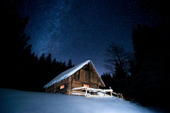 Beautiful wooden house in the winter forest under the stars stock image