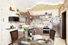 Beautiful wooden kitchen with dinner table and stone decors Stock Photos