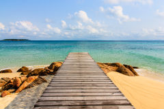 Beautiful wooden pier to blue sea. Beautiful wooden pier on beach at Monnok island, Rayong, Thailand Stock Image