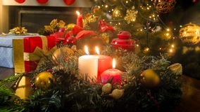 Beautiful wooden table decorated with burning candles, wreath and lanterns for celebrating Christmas Royalty Free Stock Photos