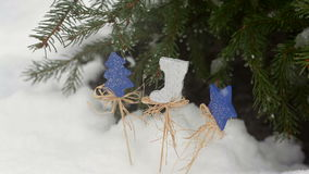 Beautiful wooden toy under the fir tree in snow in winter outdoors.  stock footage