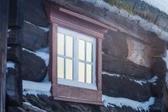 Beautiful wooden window with frozen ice flowers in Norwegian town. Beautiful winter day. Architecture detail Stock Image
