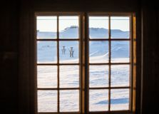Beautiful wooden window with frozen ice flowers in Norwegian town. Beautiful winter day. Architecture detail Stock Photos
