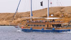 Beautiful Wooden Yacht with Tourists is Sailing in the Stormy Sea on the background of Rocks. Egypt. Sharm El Sheikh. Pirate ship with masts and a flag moves stock video