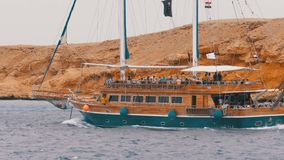 Beautiful wooden yacht with tourists is sailing in the stormy sea on the background of rocks. Egypt. Sharm El Sheikh. Pirate ship with masts and a flag moves stock video footage