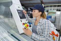 Beautiful worker operating machine in factory. Beautiful worker operating a machine in a factory Royalty Free Stock Photo