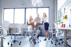 Beautiful workers smiling and throwing documents on the office background. Successful contract concept. stock photo