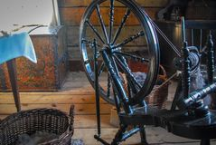 Antique Spinning Wheel with an Intricately Carved Trunk and a basket of Wool royalty free stock photo