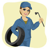 Beautiful working woman in car repair service holding tyre and wheel wrench. Beautiful young working woman in car repair service holding wheel and wrench Stock Photo