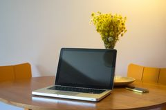 Beautiful workspace with soft lights and flowers. A beautiful workspace with a notebook over the desk and decorative flowers. Very soft lights coming from above Royalty Free Stock Image