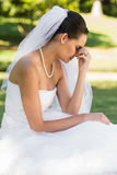 Beautiful worried bride sitting at park Royalty Free Stock Image