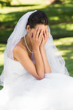 Beautiful worried bride sitting at park Stock Photos
