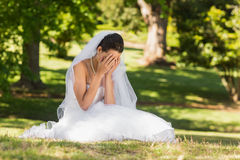 Beautiful worried bride sitting at park Stock Images