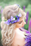 Beautiful wreath on a had of woman. Beautiful purple wreath on a blonde  had of young woman Royalty Free Stock Photo