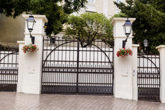 Beautiful wrought iron security gate. Beautiful wrought iron gate with street lanterns and pending flowers royalty free stock image