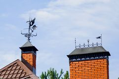 A beautiful wrought iron weathercock on the roof of the house. stock photo