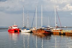 Yachts on the sea moorage. Beautiful yachts on the dock in the rays of the setting sun stock image