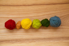 A beautiful yarn balls in vibrant colorful tones. On wooden background Royalty Free Stock Image