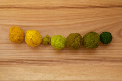 A beautiful yarn balls in vibrant colorful tones. On wooden background Royalty Free Stock Photography