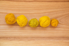 A beautiful yarn balls in vibrant colorful tones. On wooden background Royalty Free Stock Images