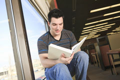 A beautiful 20 yars old men student studying. A beautiful 20 yars old man student read a book close to a window Stock Photos